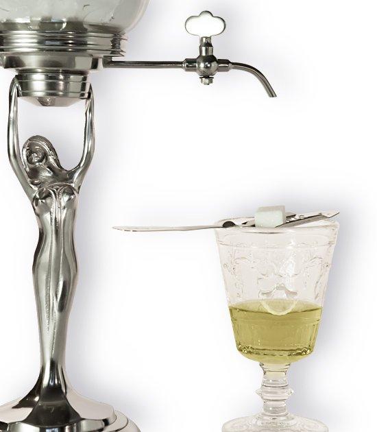 Detail absintové fontány, sklenice absintu a lžičky s cukrem.