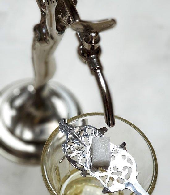 Absintová lžička wormwood s cukrem na sklenici absintu a kapající kohoutek absintové fontány.