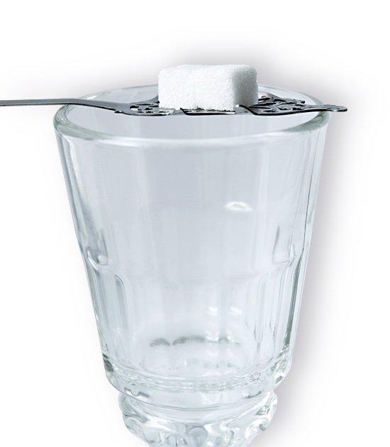 Detail absintové sklenice Pontarlier se lžičkou na absint a cukrem.