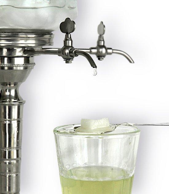 Detail kohoutku absintové fontány a sklenice se lžičkou, cukrem a s absintem